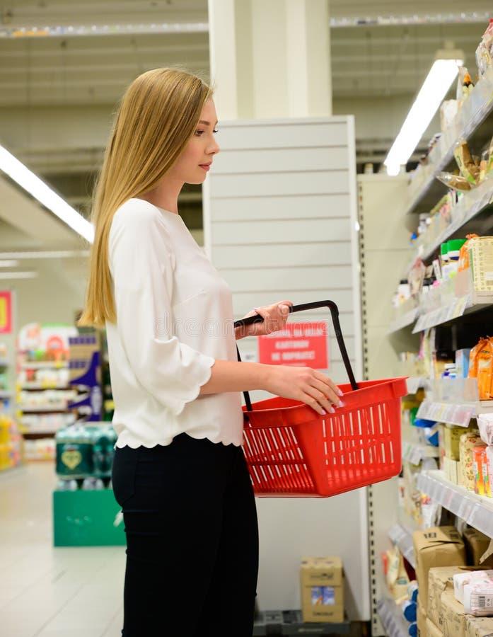 Mujer joven hermosa que hace compras en el colmado, tomando la comida del estante fotos de archivo