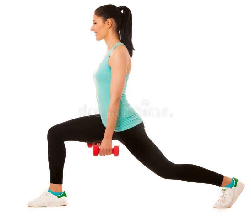 Mujer joven hermosa que hace ejercicio de la estocada con pesas de gimnasia rojas adentro fotografía de archivo