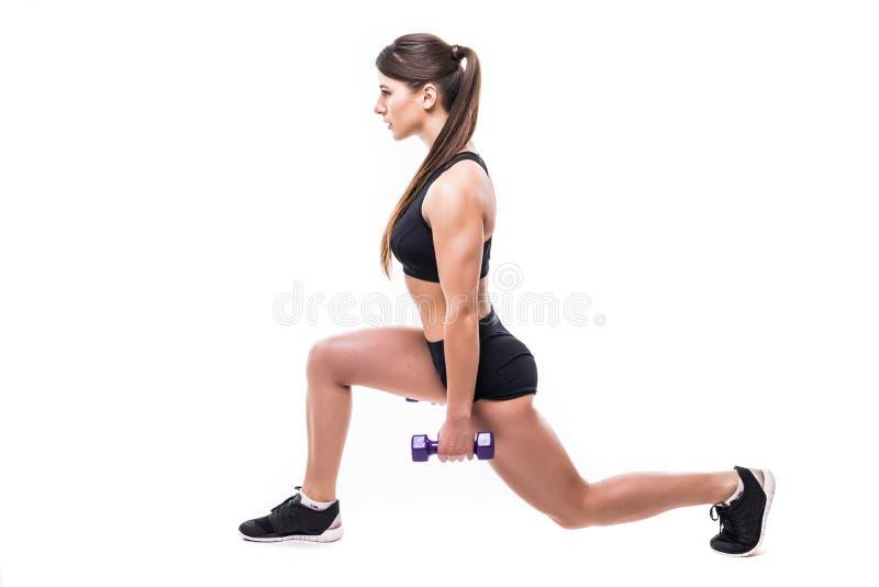 Mujer joven hermosa que hace ejercicio de la estocada con pesas de gimnasia rojas en el gimnasio de la aptitud aislado sobre el f imagenes de archivo