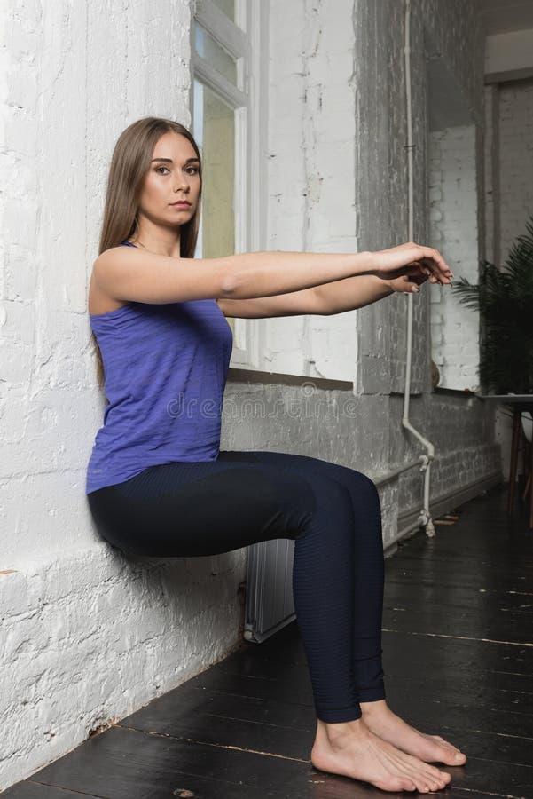 Mujer joven hermosa que hace ejercicios en casa foto de archivo libre de regalías