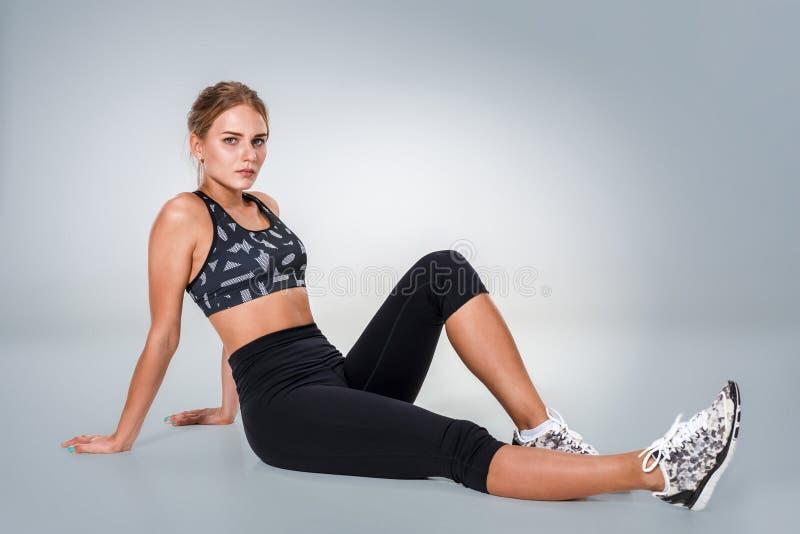 Mujer joven hermosa que hace ejercicios en el piso para consolidar foto de archivo