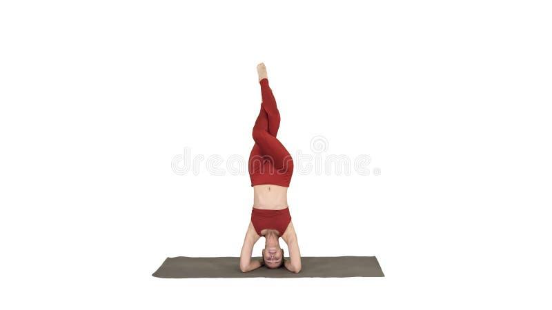 Mujer joven hermosa que hace la variaci?n del ejercicio de la yoga del headstand apoyado, sirsasana del salamba del garuda con la imágenes de archivo libres de regalías