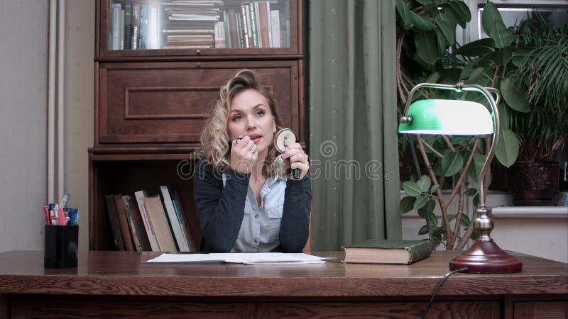 Mujer joven hermosa que hace su maquillaje en la tabla en casa fotografía de archivo