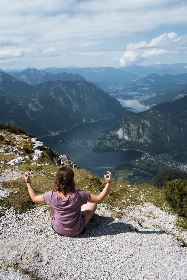 Mujer joven hermosa que hace yoga en la montaña sobre Hallstatt fotos de archivo
