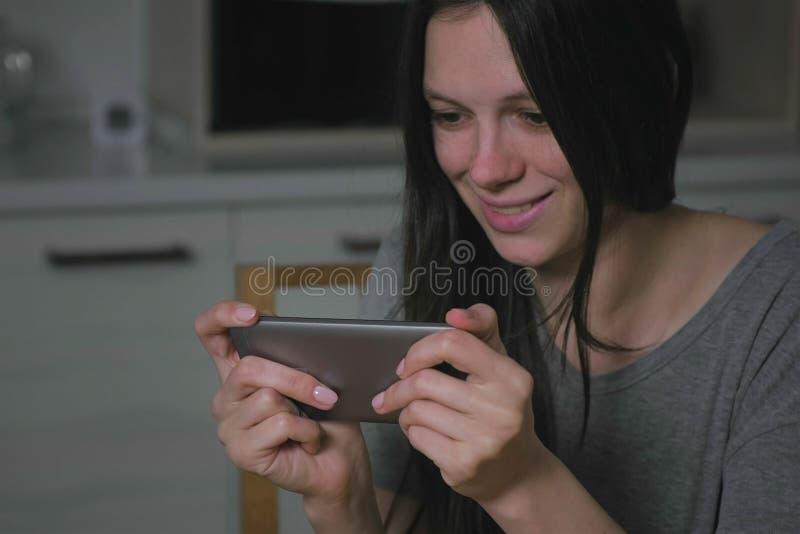 Mujer joven hermosa que juega cautelosamente a juegos en el teléfono móvil en la cocina en la noche foto de archivo