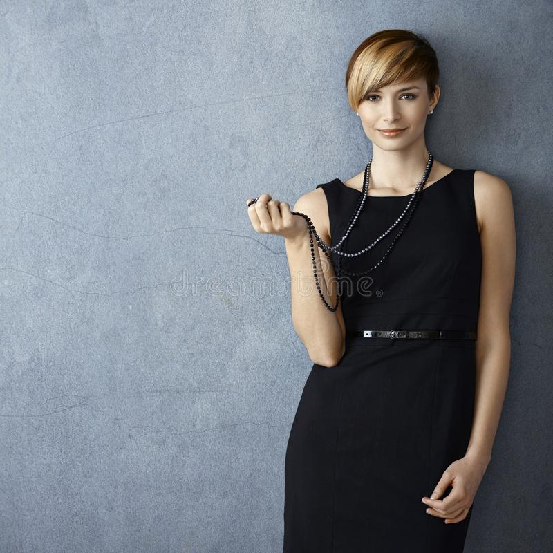 Mujer joven hermosa que juega con el collar de la perla fotografía de archivo