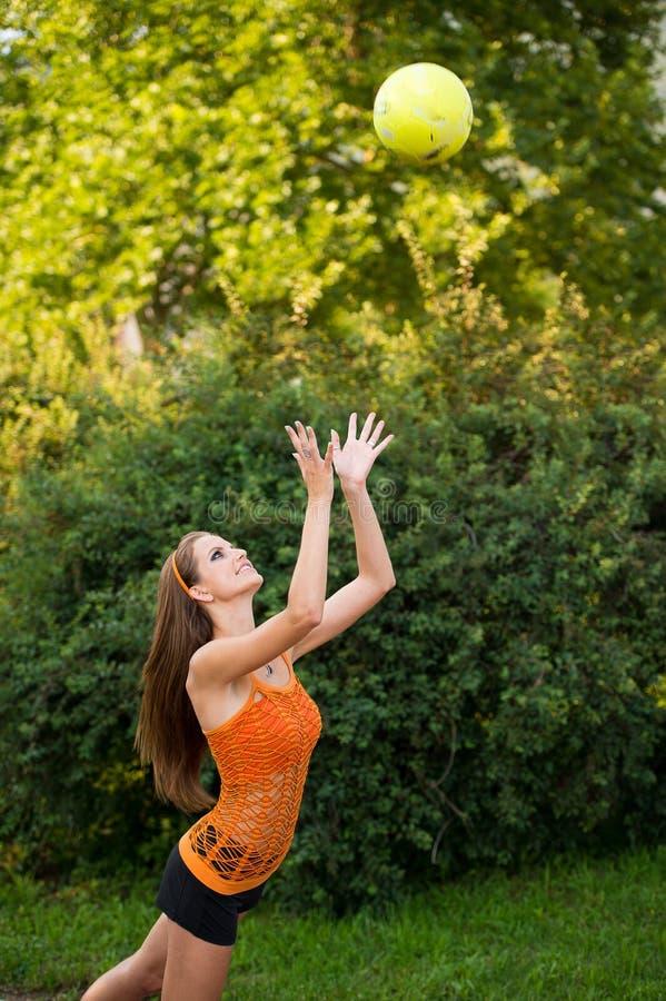 Mujer joven hermosa que juega con la bola al aire libre en parque fotos de archivo
