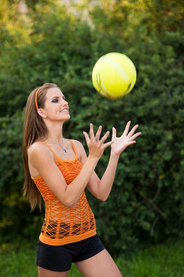 Mujer joven hermosa que juega con la bola al aire libre en parque fotografía de archivo