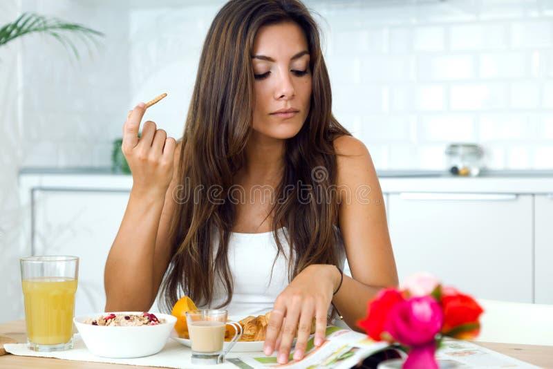 Mujer joven hermosa que lee las noticias y que goza del desayuno fotos de archivo libres de regalías
