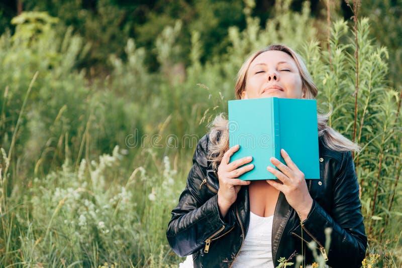 Mujer joven hermosa que lee un libro en el césped con el Sun imagenes de archivo