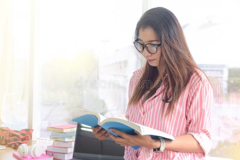 Mujer joven hermosa que lee un libro para descubrir la información en la biblioteca Gente, conocimiento, educación y concepto de  foto de archivo libre de regalías