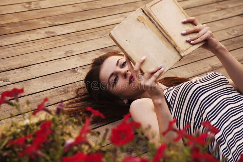 Mujer joven hermosa que lee un libro relájese, romance, poesía, r fotos de archivo