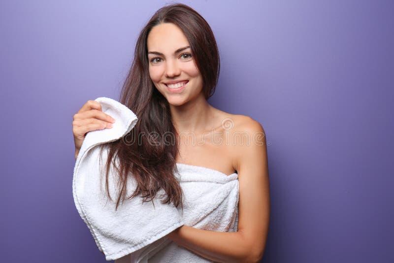 Mujer joven hermosa que limpia el pelo con la toalla en fondo del color imagen de archivo libre de regalías