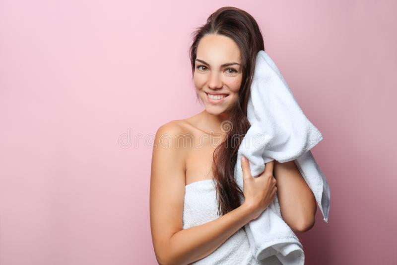 Mujer joven hermosa que limpia el pelo con la toalla en fondo del color imágenes de archivo libres de regalías