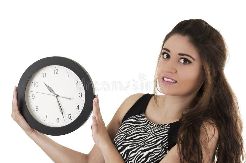 Mujer joven hermosa que lleva a cabo tiempo de reloj redondo grande fotografía de archivo libre de regalías