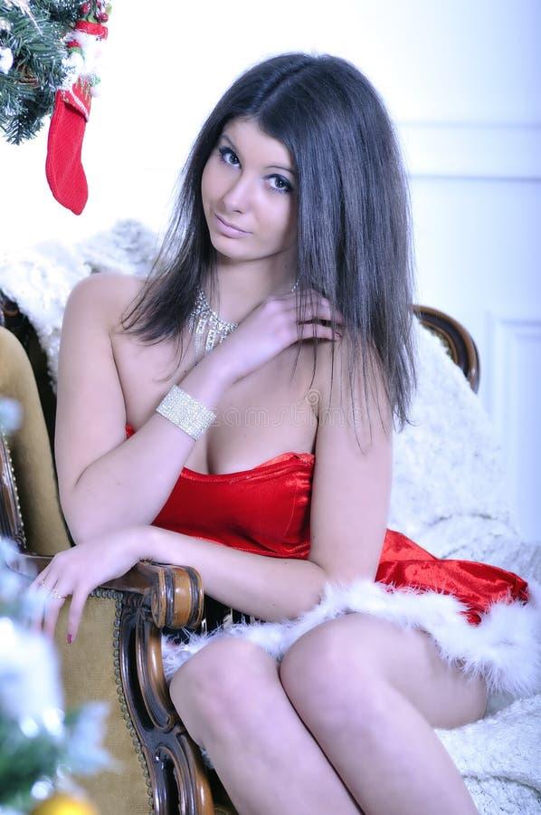 Mujer joven hermosa que lleva en el traje de Papá Noel imagenes de archivo
