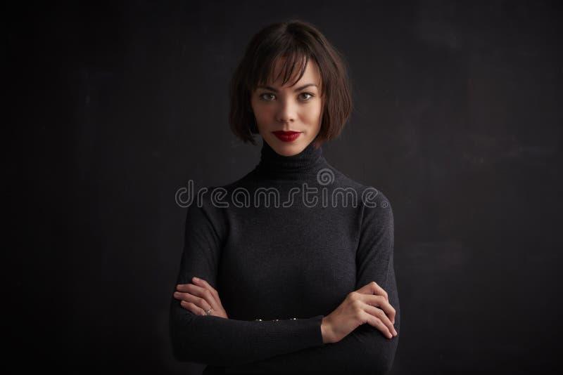 Mujer joven hermosa que lleva la barra de labios roja mientras que presenta en el fondo oscuro foto de archivo libre de regalías