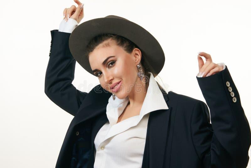 Mujer joven hermosa que lleva la chaqueta y el sombrero negros del traje imagen de archivo