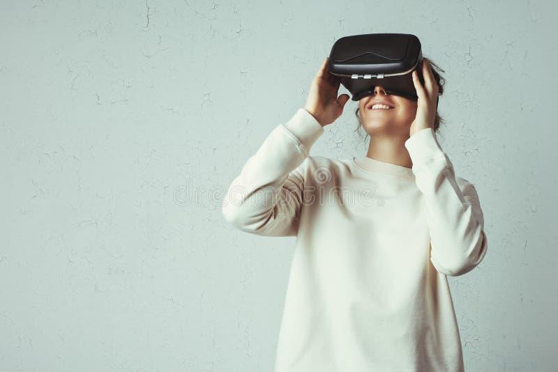Mujer joven hermosa que lleva las auriculares virtuales Inconformista sonriente que usa los vidrios de VR Suéter en blanco imagen de archivo