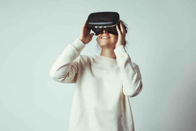 Mujer joven hermosa que lleva las auriculares virtuales Inconformista sonriente que usa los vidrios de VR Suéter en blanco Fondo  foto de archivo libre de regalías
