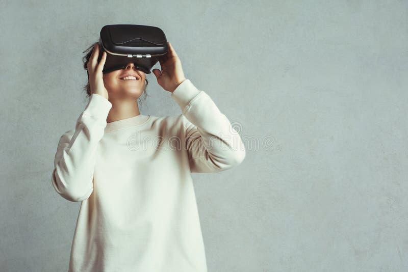 Mujer joven hermosa que lleva las auriculares virtuales Inconformista sonriente que usa los vidrios de VR Suéter en blanco Fondo  imagenes de archivo