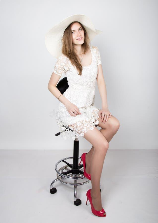 Mujer joven hermosa que lleva un vestido blanco y los tacones altos, sentándose en una silla imagenes de archivo