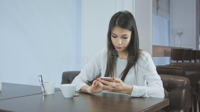 Mujer joven hermosa que manda un SMS en smartphone en un café fotos de archivo libres de regalías