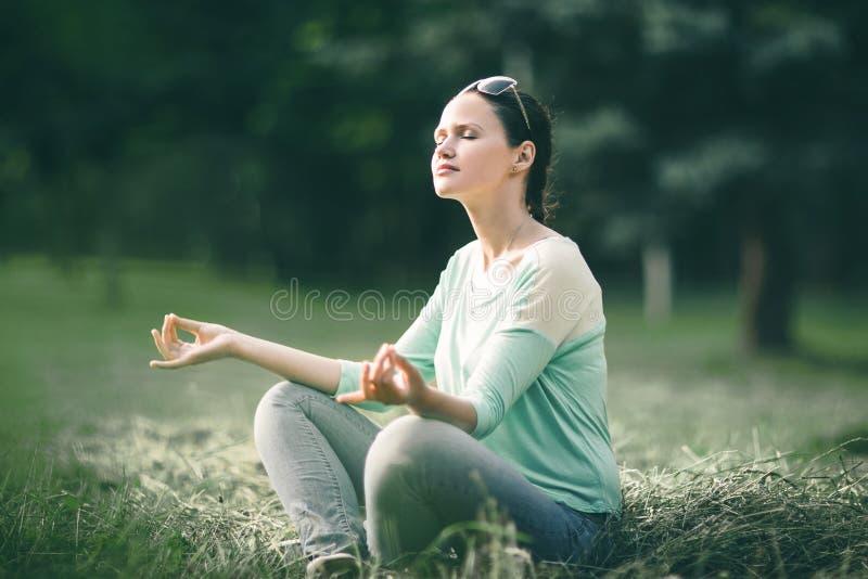 Mujer joven hermosa que medita en la posición de Lotus en parque de la mañana foto de archivo