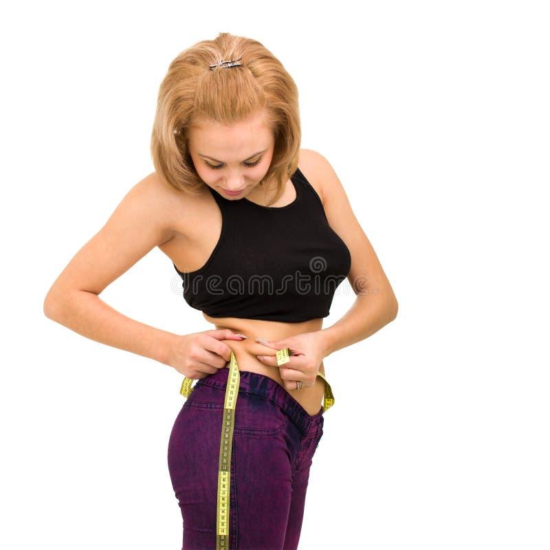 Mujer joven hermosa que mide su cintura fotos de archivo