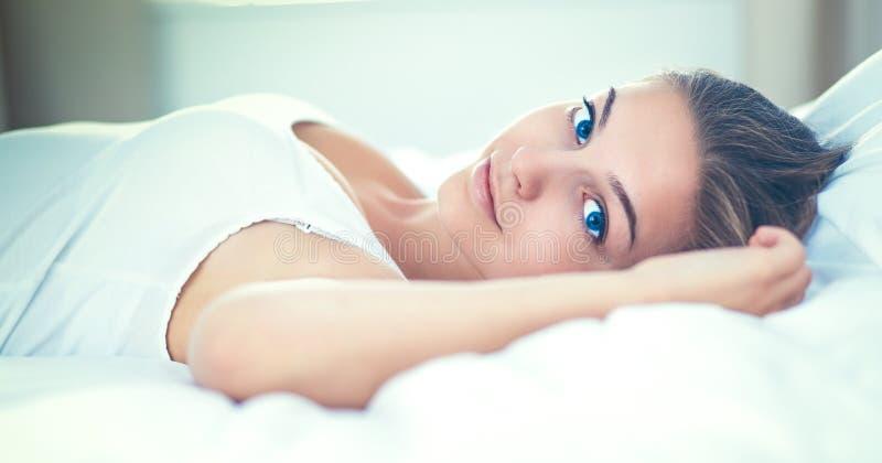 Mujer joven hermosa que miente en cama comfortablemente y dichosamente imagen de archivo