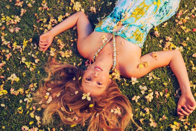 Mujer joven hermosa que miente en flores imágenes de archivo libres de regalías