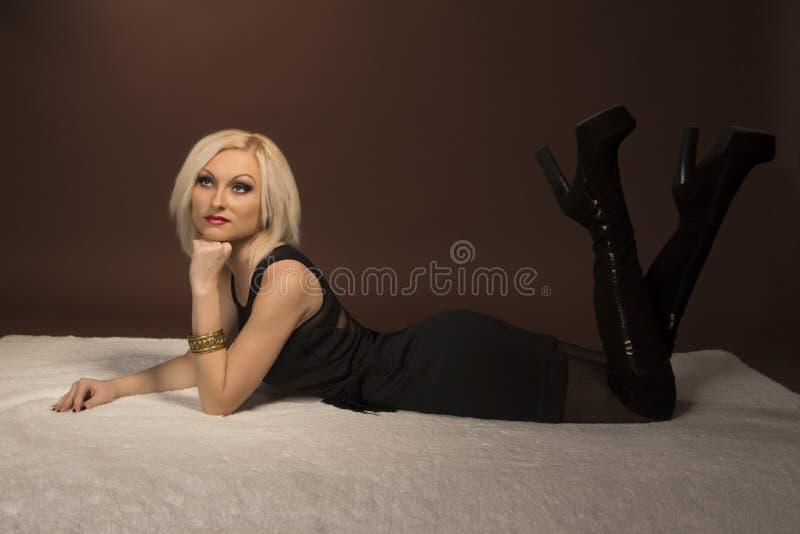 Mujer joven hermosa que miente en la alfombra blanca imágenes de archivo libres de regalías