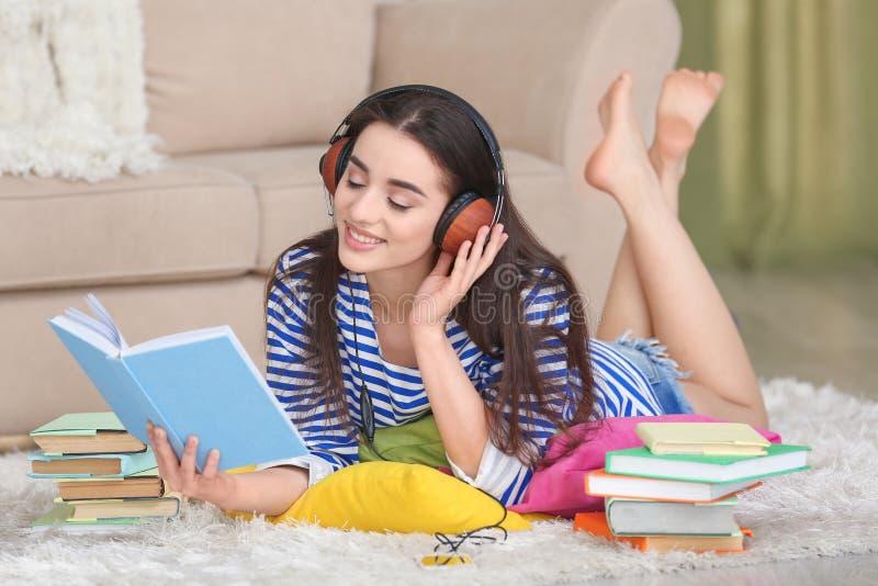 Mujer joven hermosa que miente en piso y que escucha el audiolibro imagen de archivo