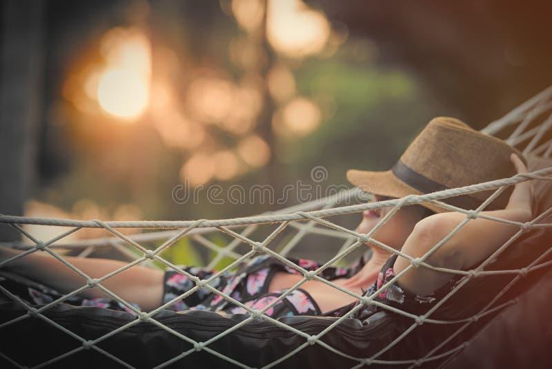 Mujer joven hermosa que miente en una hamaca y que se relaja con el sombrero o imagen de archivo libre de regalías