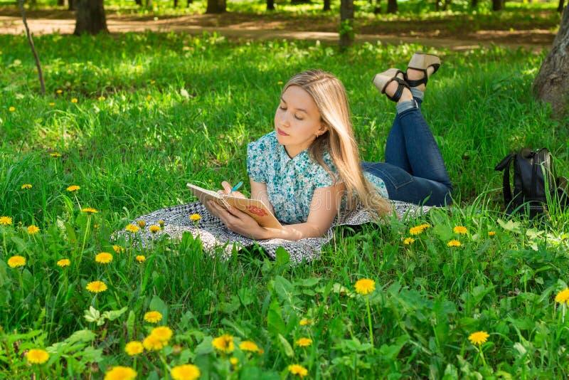 Mujer joven hermosa que miente, pensando y escribiendo en su diario en la hierba con las flores Front View imagenes de archivo