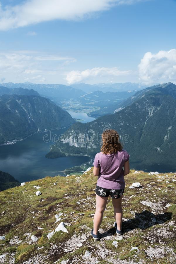 Mujer joven hermosa que mira el lago en las montañas imagenes de archivo