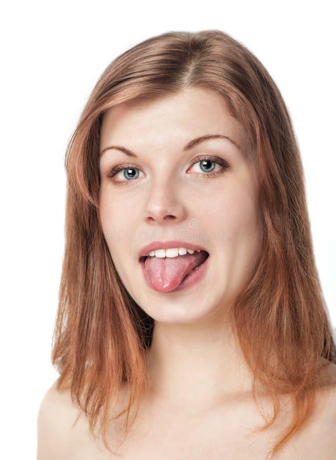 Mujer joven hermosa que muestra la lengua fotografía de archivo
