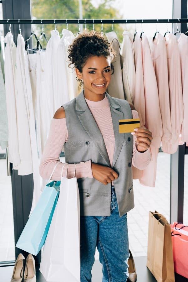 mujer joven hermosa que muestra la tarjeta de crédito imagen de archivo libre de regalías