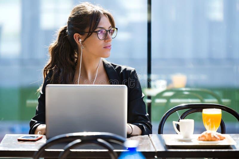 Mujer joven hermosa que parece oblicua mientras que trabaja con su ordenador portátil en una cafetería fotos de archivo libres de regalías