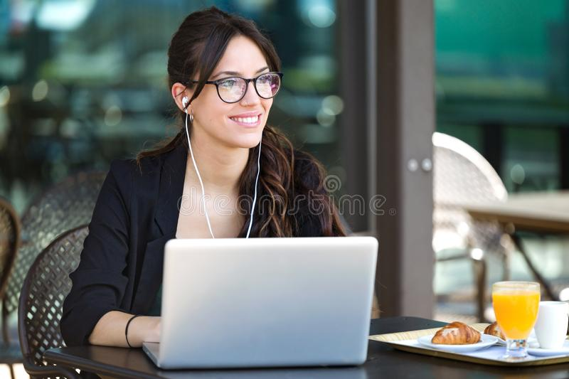 Mujer joven hermosa que parece oblicua mientras que trabaja con su ordenador portátil en una cafetería fotografía de archivo libre de regalías