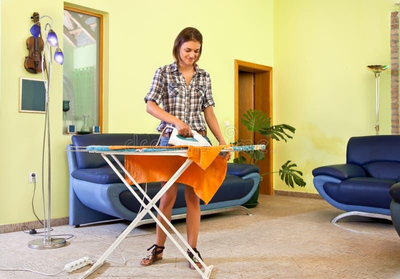 Mujer joven hermosa que plancha su ropa en casa. imagenes de archivo