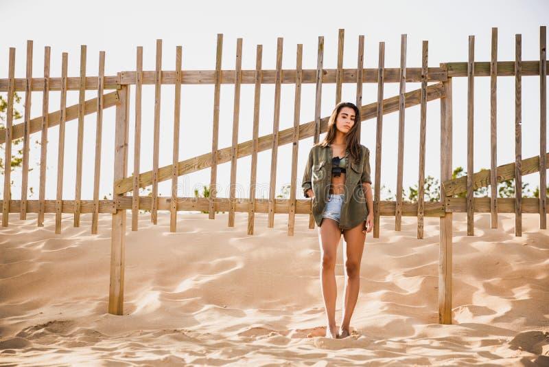 Mujer joven hermosa que presenta cerca de una cerca de madera fotografía de archivo libre de regalías