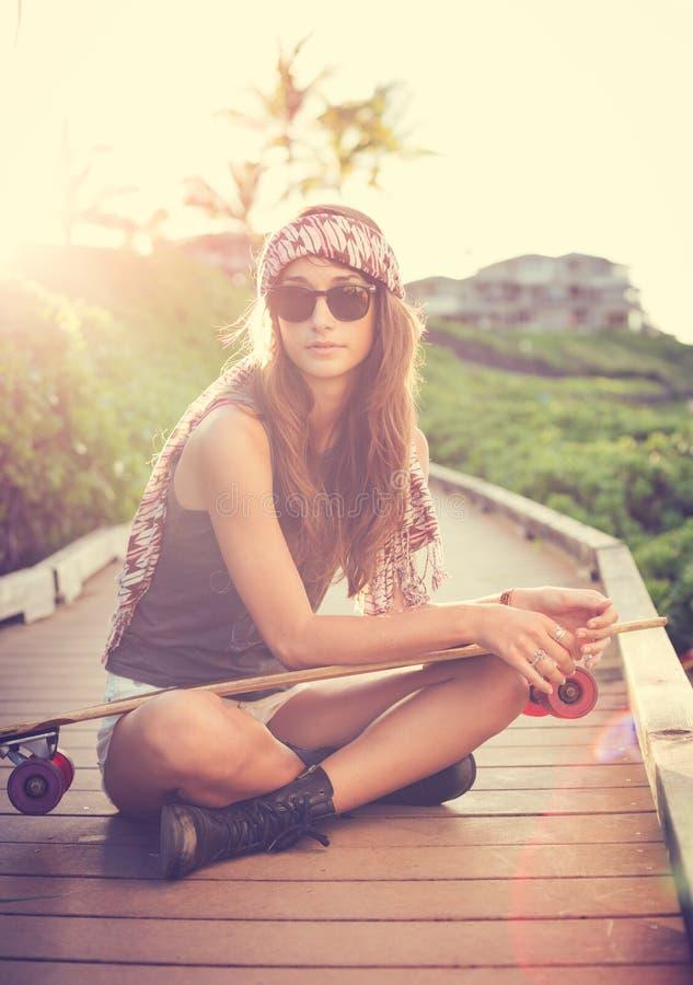Mujer joven hermosa que presenta con un monopatín imagen de archivo