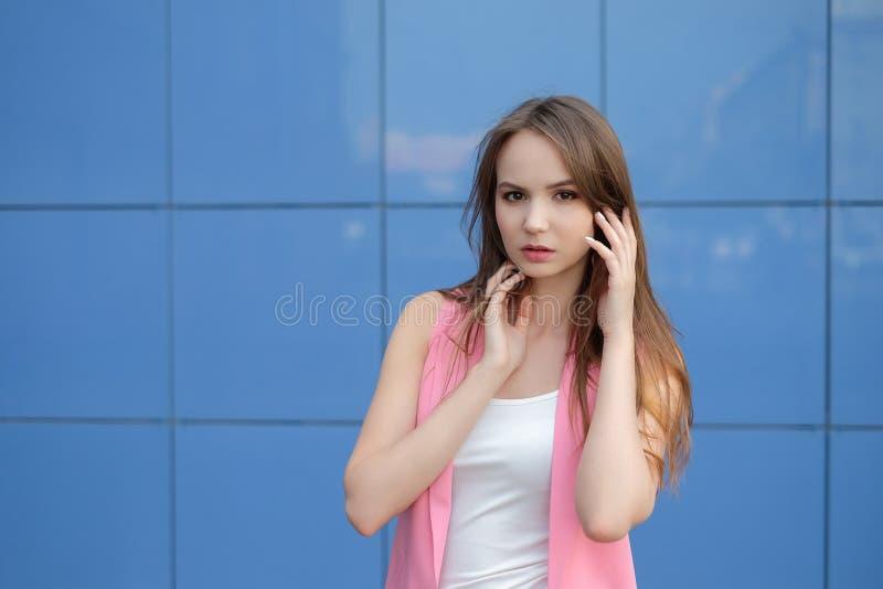 Mujer joven hermosa que presenta contra un fondo azul de la teja fotos de archivo