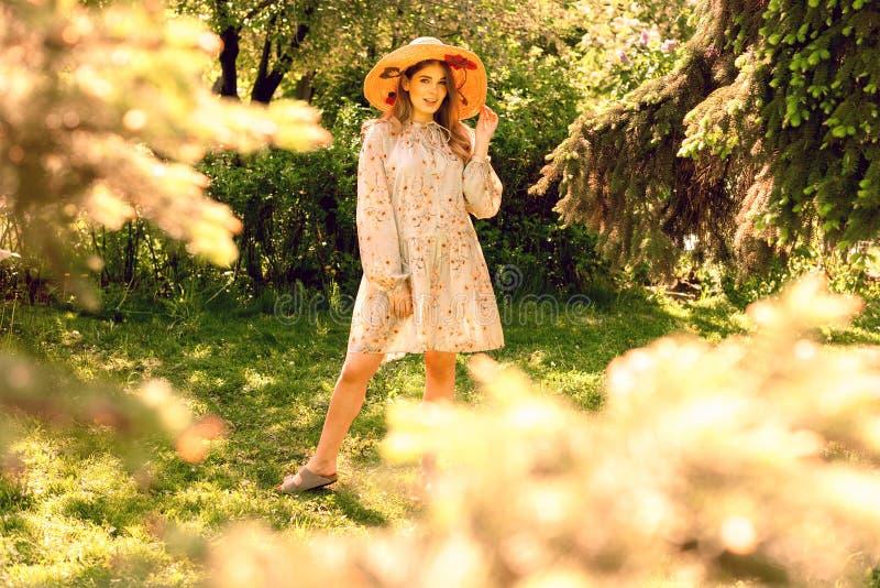 Mujer joven hermosa que presenta en el parque Sombrero y vestido ligero del verano fotos de archivo