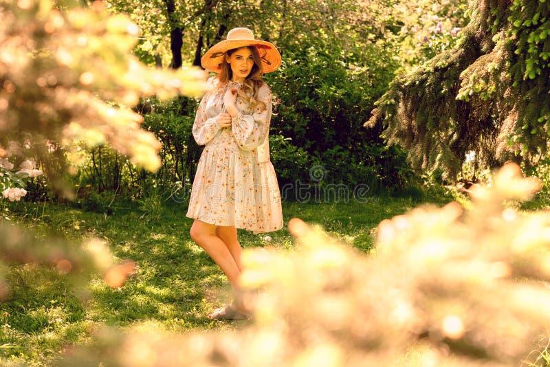 Mujer joven hermosa que presenta en el parque Vestido y sombrero del verano fotos de archivo libres de regalías