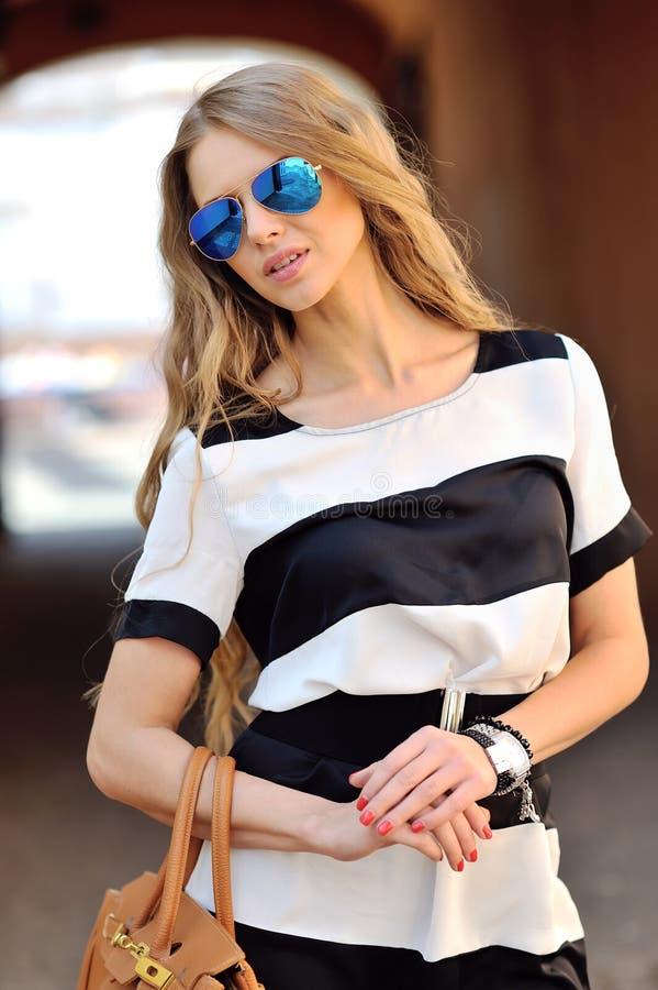 Mujer joven hermosa que presenta en gafas de sol imagen de archivo