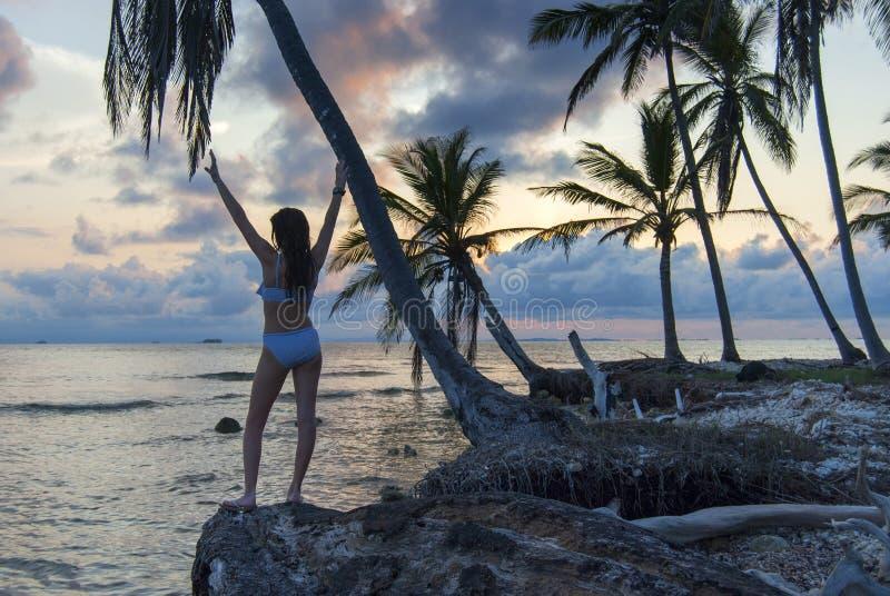 Mujer joven hermosa que presenta en la playa en una isla del paraíso en Panamá, en la puesta del sol fotografía de archivo