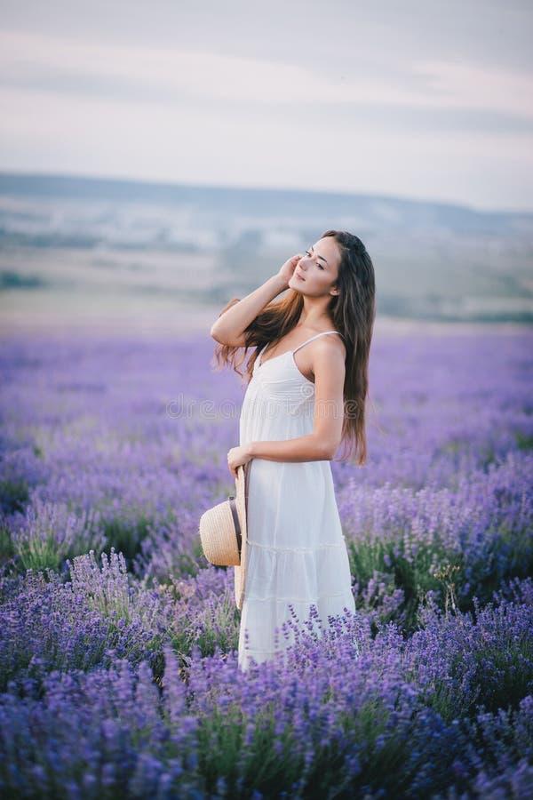 Mujer joven hermosa que presenta en un campo de la lavanda fotografía de archivo