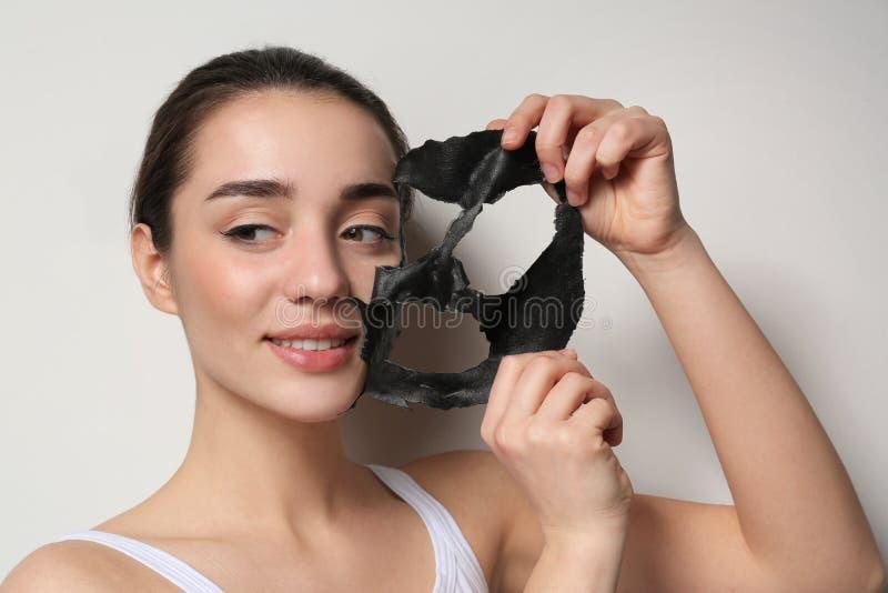 Mujer joven hermosa que quita la m?scara negra de su cara en blanco fotos de archivo libres de regalías
